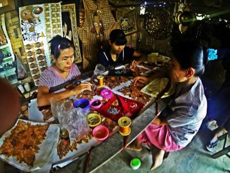 Burmese women creating intricate patterns